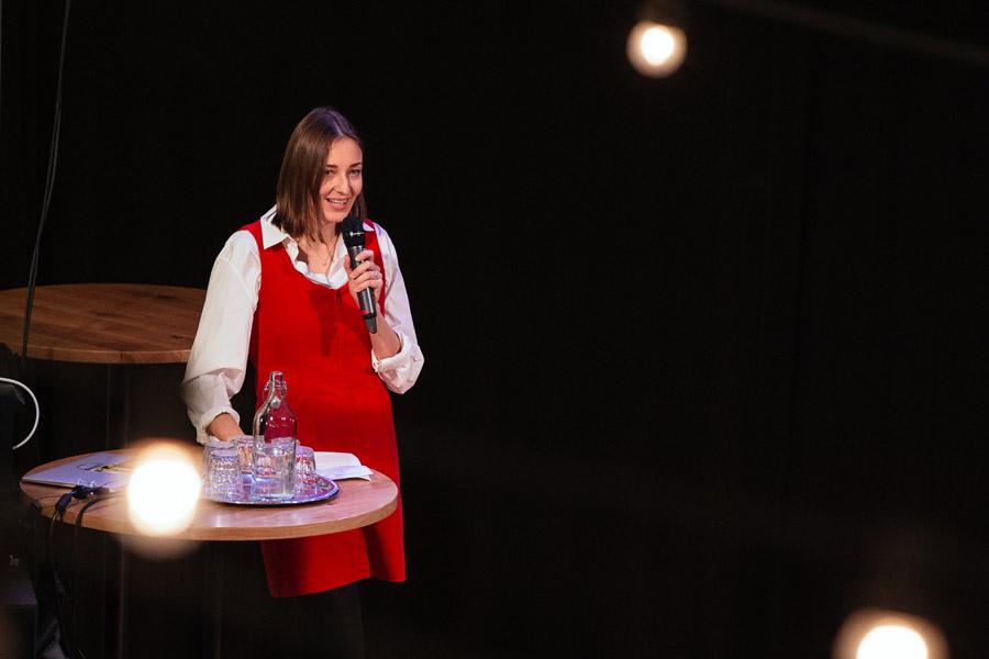 Nainen seisoo lavalla ja puhuu mikrofoniin.